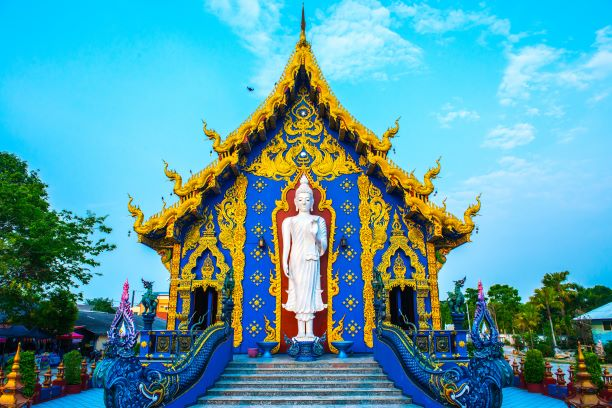 The White Standing Buddha behide ubosot the blue temple
