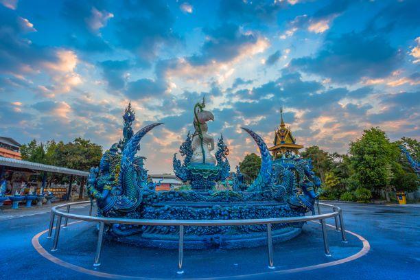 Buddha Statue in front of Chiang Rai Blue Temple or Wat Rong Seua Ten