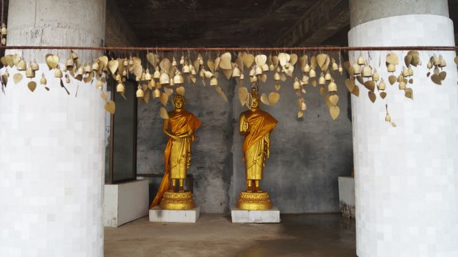 Two antique golden Buddha statues behind golden wind bells in the Big Buddha temple in Phuket, Thailand
