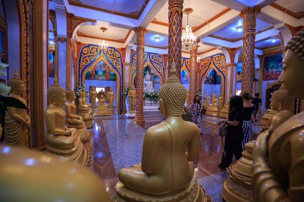 inside of one of the buildings in Wat Chalong contains many golden buddha statues