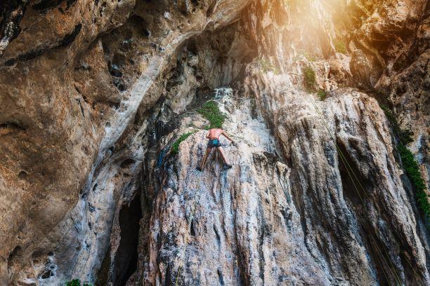 Adventure man traveler climbing on limestone cliff in Krabi