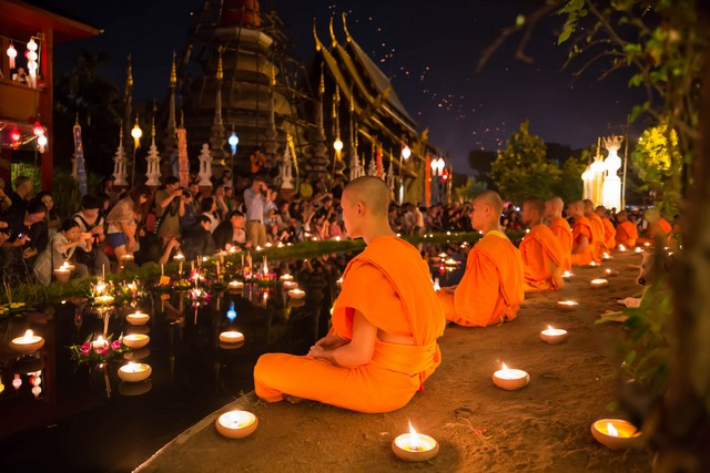 Buddhist monk fire candles to the Buddha
