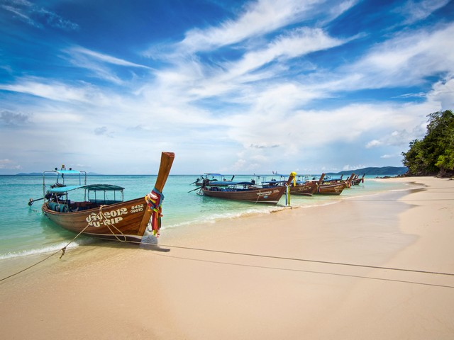 Long-tail boats on the shore of idyllic Bamboo Island, Koh Phi Phi, Thailand
