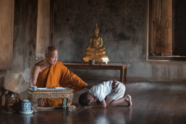 The boy in school uniform pay-respect wai-monks to achieve happiness