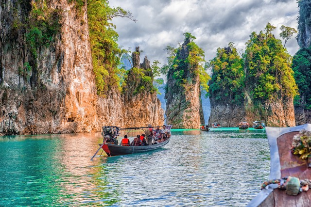 Tourists riding a boat to see the beauty of the rock cliff
