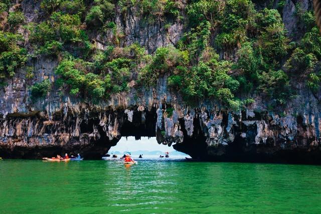 Cave,Tourists kayaking through limestone cliffs in Phang-nga Bay of Thailand