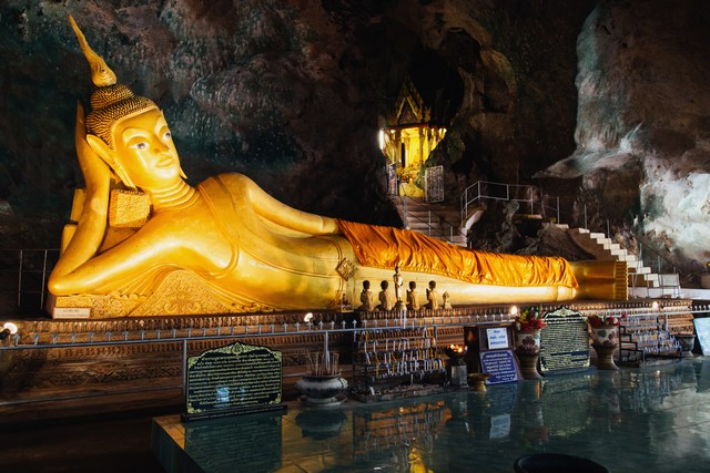 Wat Tham Suwan Khuha cave. The golden reclining Buddha is a tourist attraction in Phang Nga